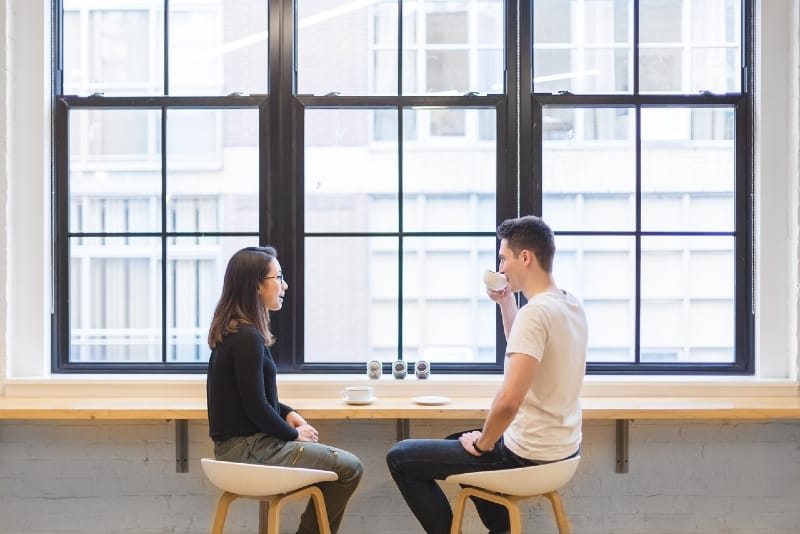 man drinking coffee while sitting near woman