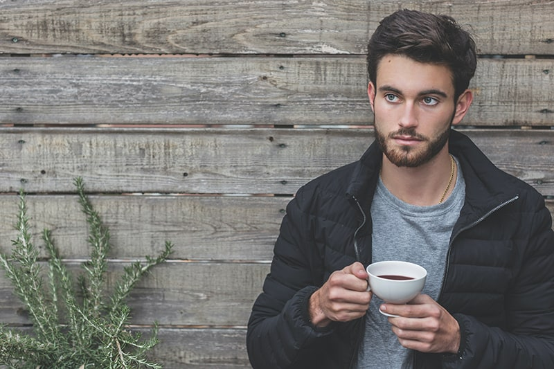 man holding a coffee cup while standing near wooden wall