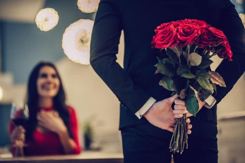 Man holding flowers at his back in front of woman
