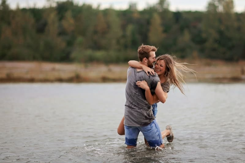 man hugging laughing woman while standing in the middle of a body of water