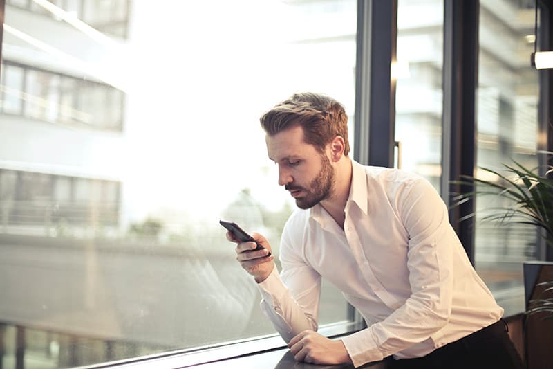 man in white dress shirt holding phone near window