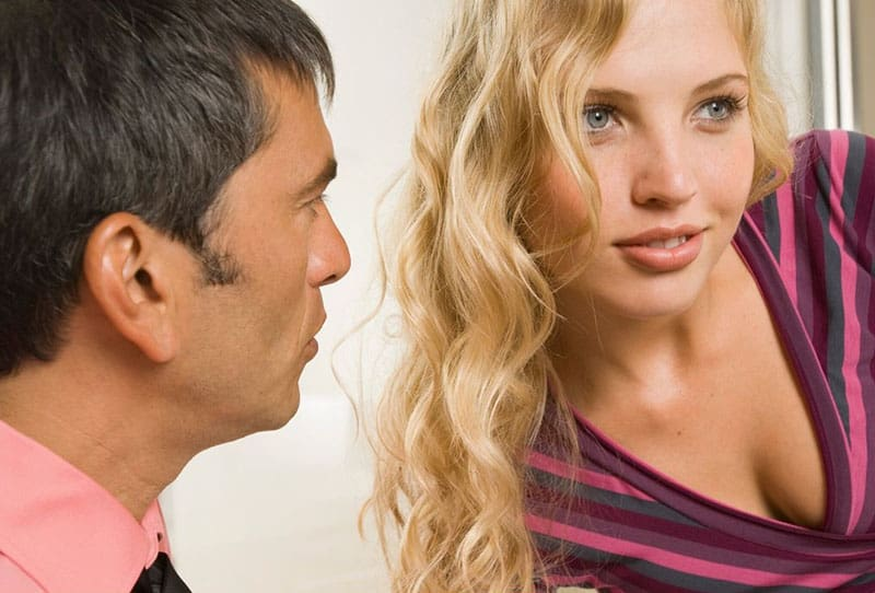 man looking at a woman with blonde curly hair