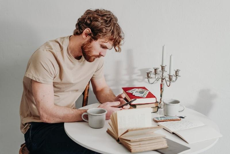 man looking at phone while sitting at table