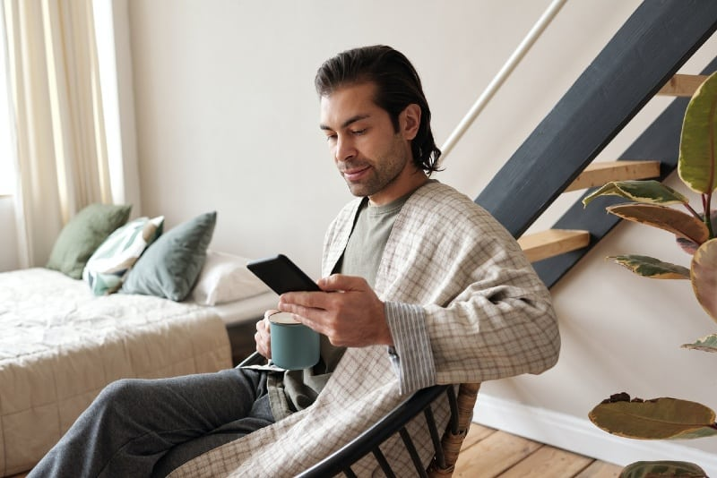 man looking at phone while having coffee