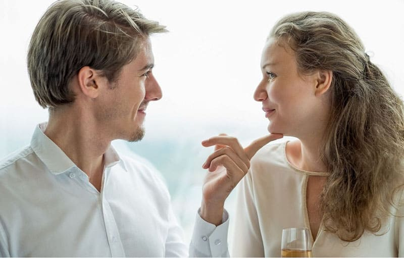 man looks at his girlfriend with love touching her chin