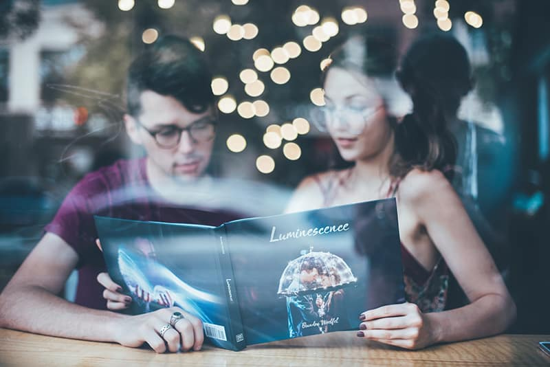 man sitting beside woman while reading catalog