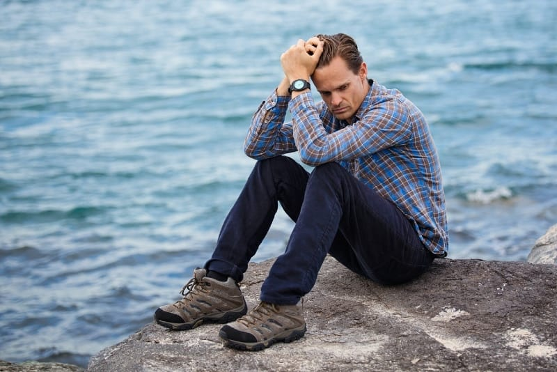 man sitting on rock near water and thinking