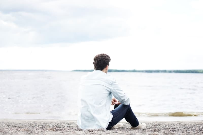 man in white shirt sitting on shore looking at water
