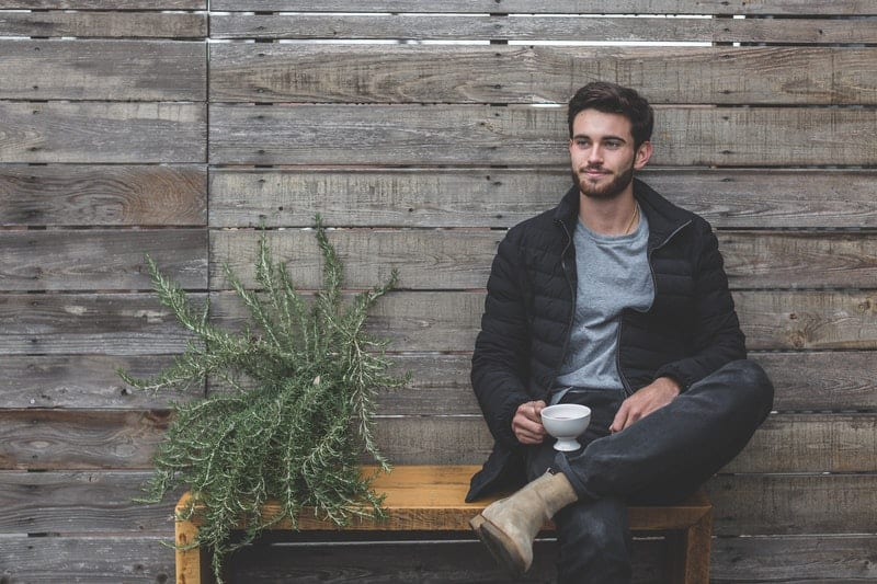 man sitting on wooden bench near plank wall and a plant beside him holding a cup