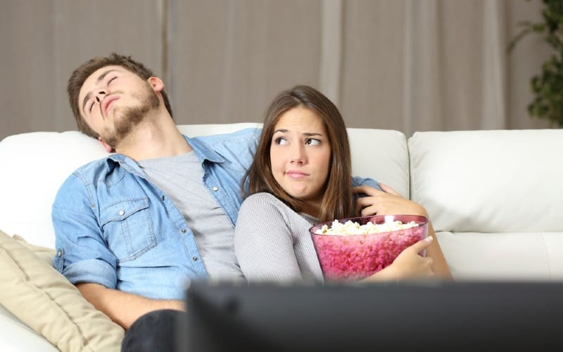 Man sleeping on couch near woman watching tv