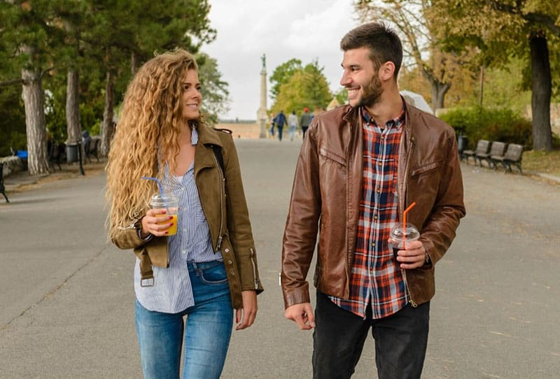 man standing beside woman holding drinks in the middle of the street