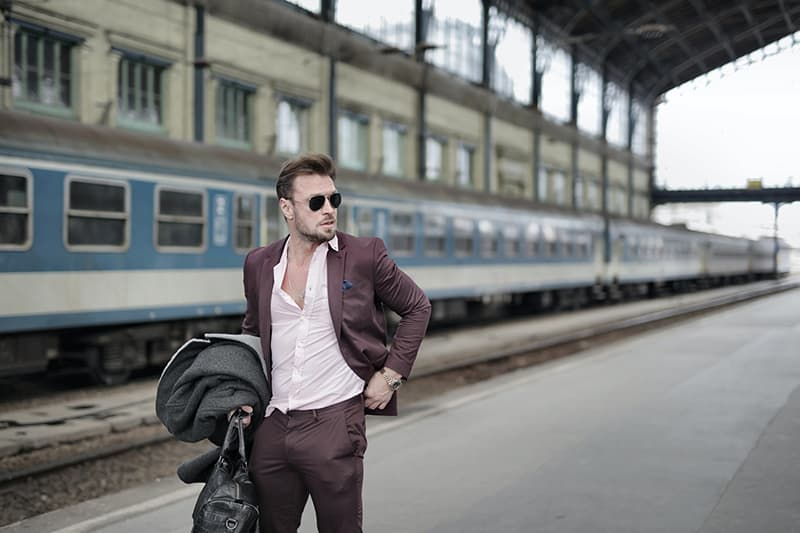 man standing on railroad platform with bag in his right hand