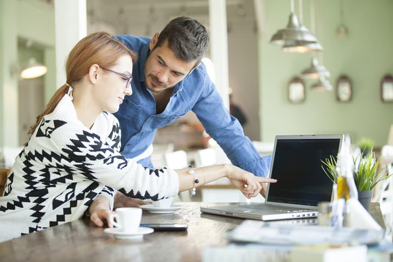 man staring at woman while she pointing him on laptop on the desk