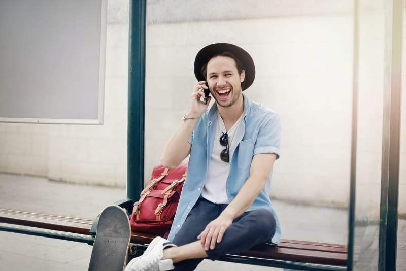 man talking on the phone while sitting on wooden bench