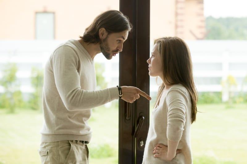 man talking to woman while standing near door
