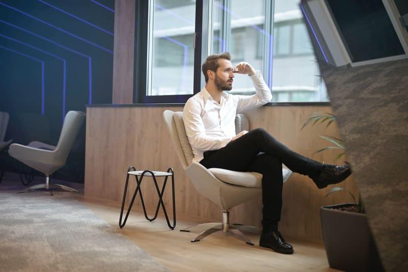 man thinking near windows while sitting on an office chair