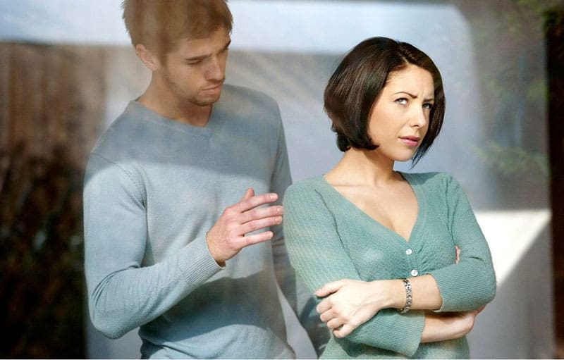 man trying to touch an angry woman