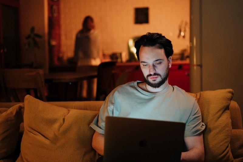 man using laptop while sitting on yellow sofa