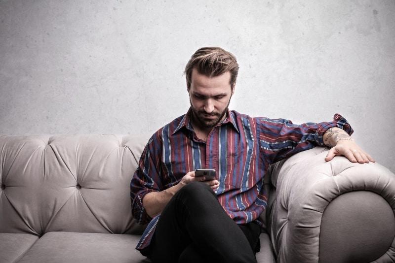 man using smartphone while sitting on white sofa