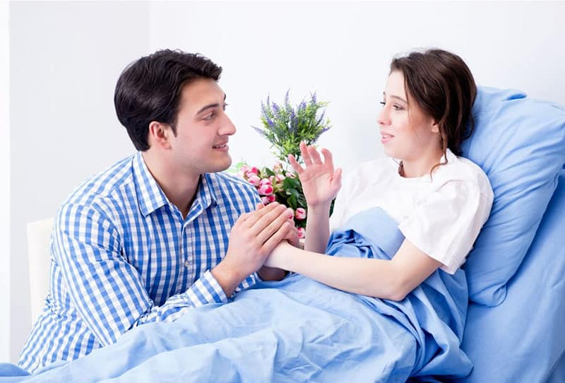 man visiting a woman lying on bed holding her hand