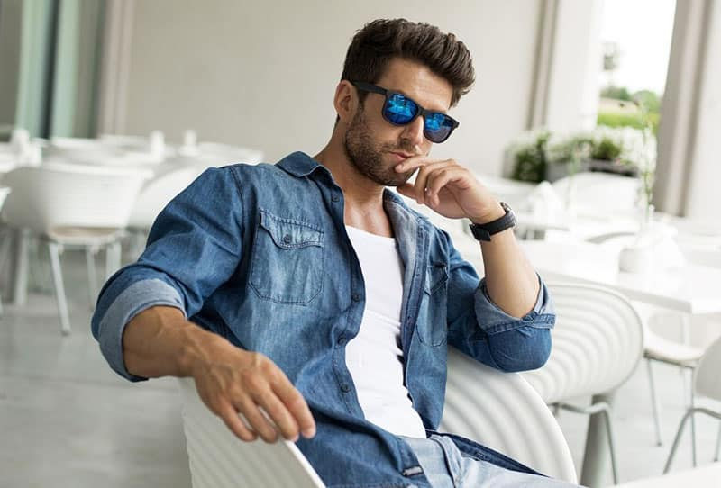 man wearing shades sitting on white chair alone inside a cafe