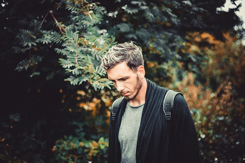 man with backpack standing near trees