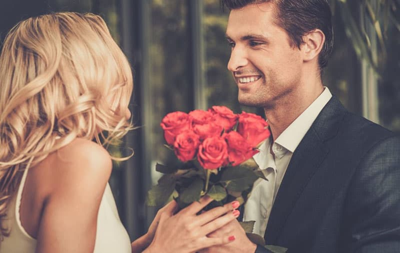 man with bunch of red roses given to a woman in white dress