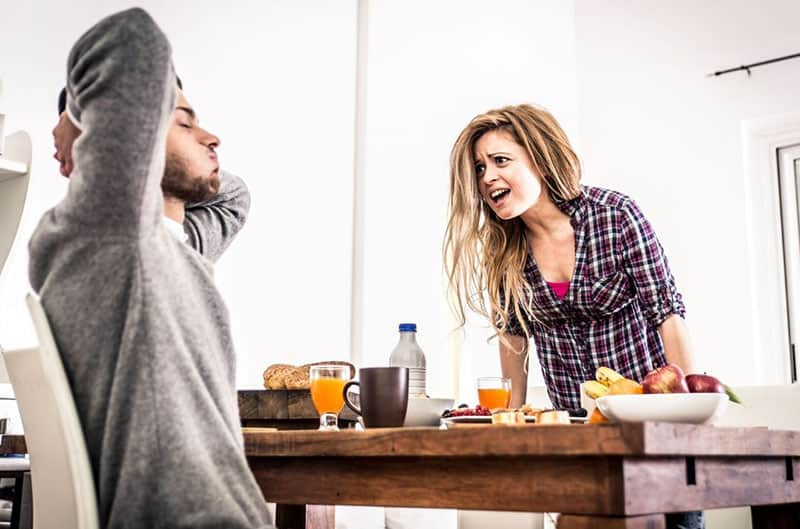 nagging woman hard in the morning in front of a man sitting in the table with breakfast food