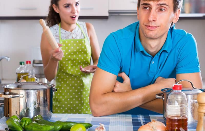 nagging woman wearing apron and holding a rolling pin to a husband wearing blue shirt
