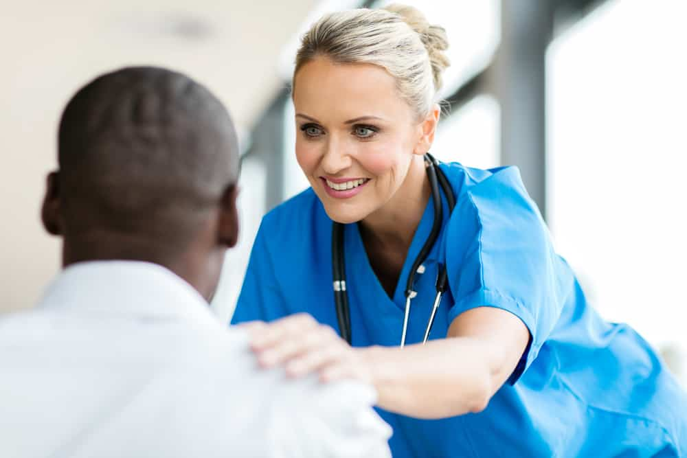 Nurse conforting patient sitting in front of her in an office