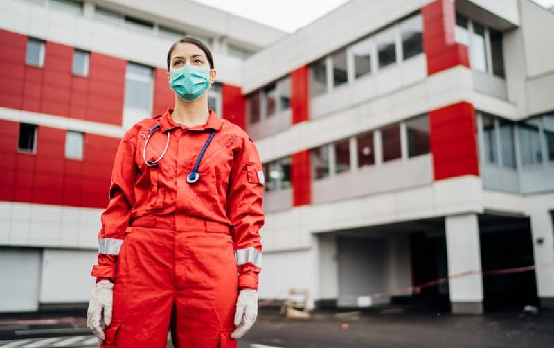 Nurse in front of hospital dressed up in red costume