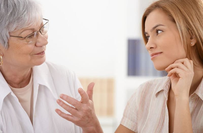older woman talking to a younger woman listening and smiling