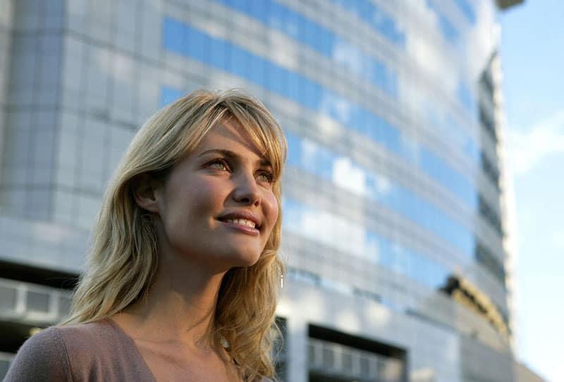 optimist woman smiling somewhere near big glass building