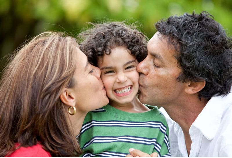 parents proud of their son giving him a kiss