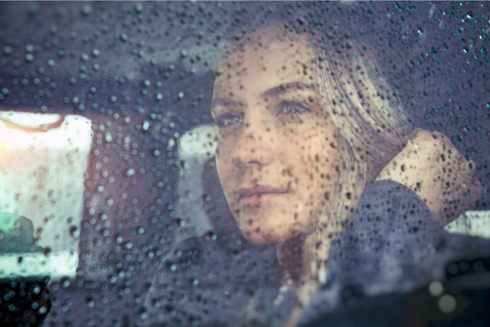 pensive blond woman sitting in the car