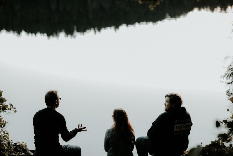 three people sitting near water and talking