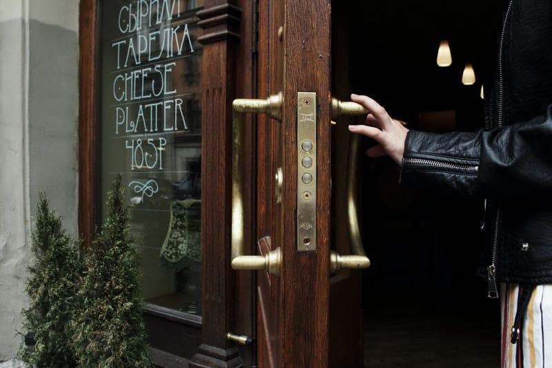 person holding door lever to open