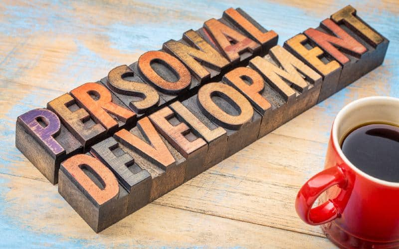 Personal development message wghit wooden vintage letters near red coffee mug