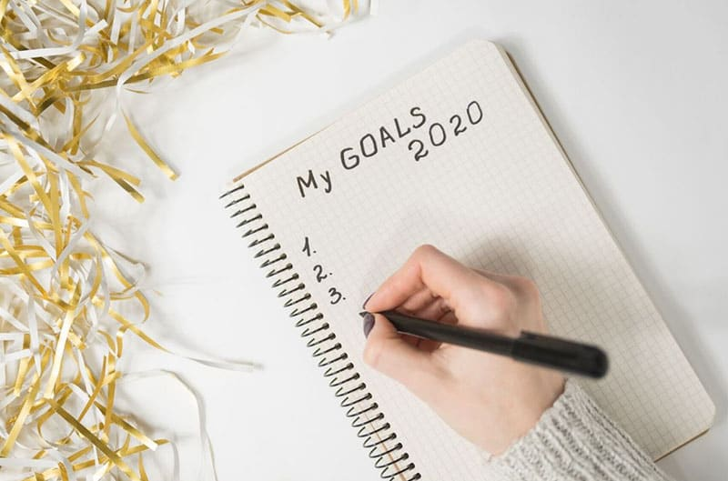 person's hand writing 2020 goals on the notebook