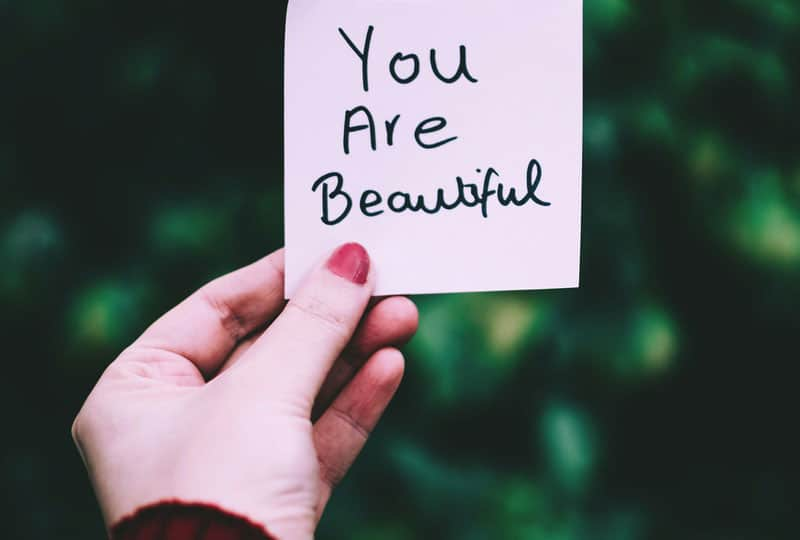 piece of paper with you are beautiful phrase written held by a person with red nail polish