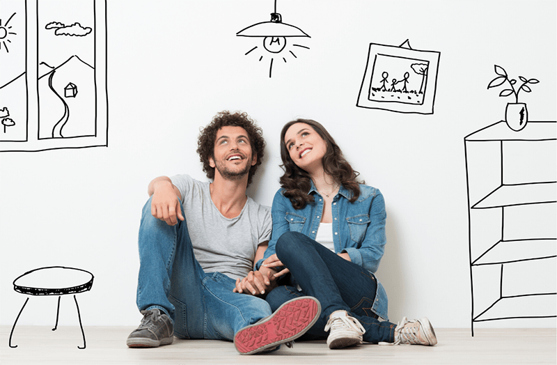 portrait of a young couple sitting on the floor dreaming with drawings of a home essentials around them