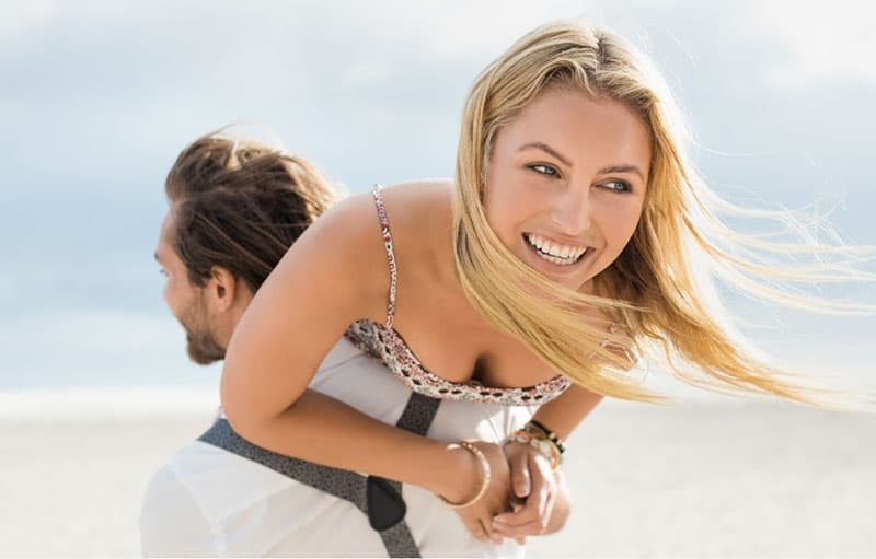 portrait of a young happy couple enjoying outdoors where man piggybacking the woman at the beach