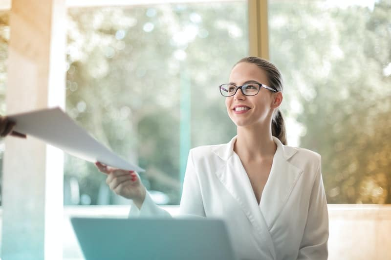 positive woman receiving paper in a positive manner inside office