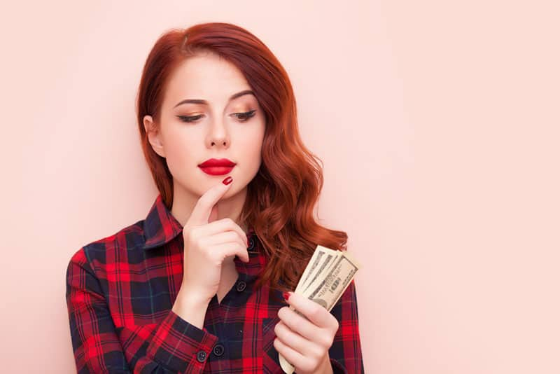 red haired woman holding money