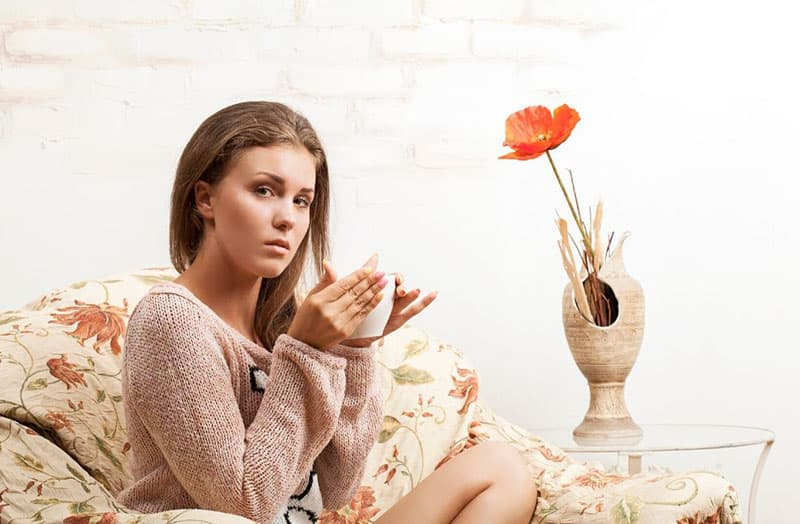 sad girl drinks tea in couch with a flower in the vase beside