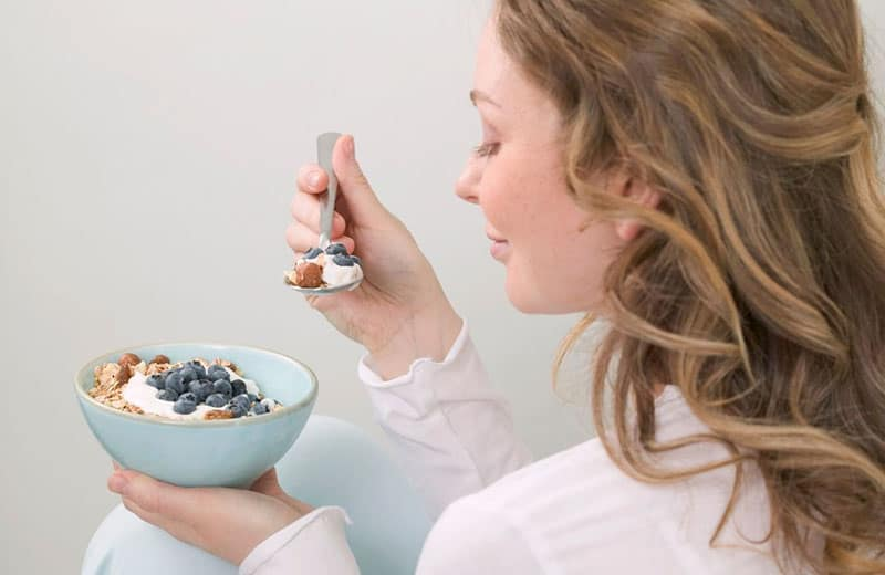 side view of a woman eating healthy smoothie with berries