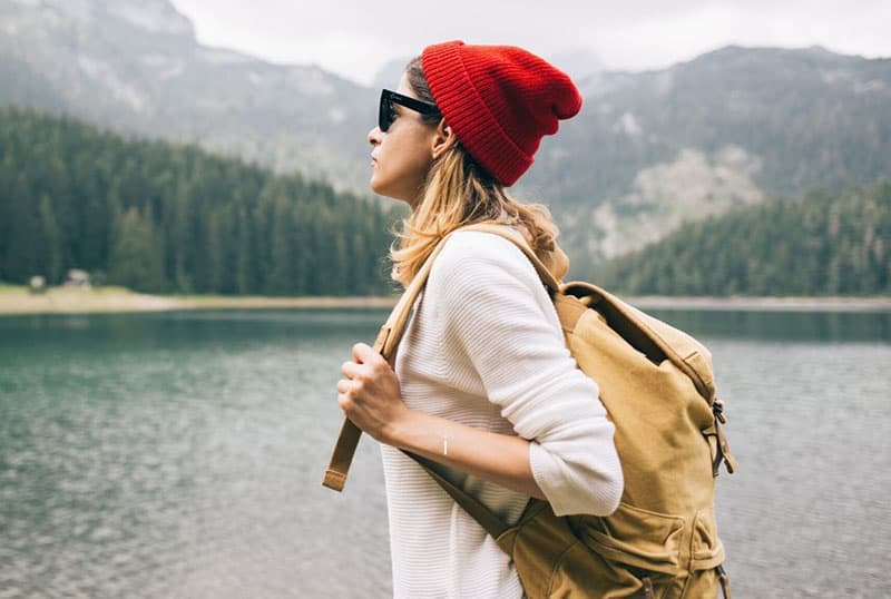 sideview of a woman with backpack standing near the lake and mountains wearing a red bonnet and sunglass