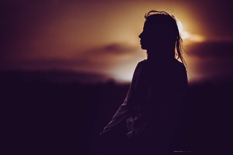 silhouette of person sitting during dusk/dawn