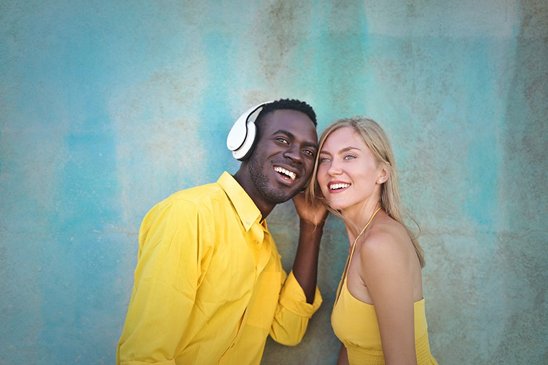 smiling man and woman standing near blue wall listening music from headphones