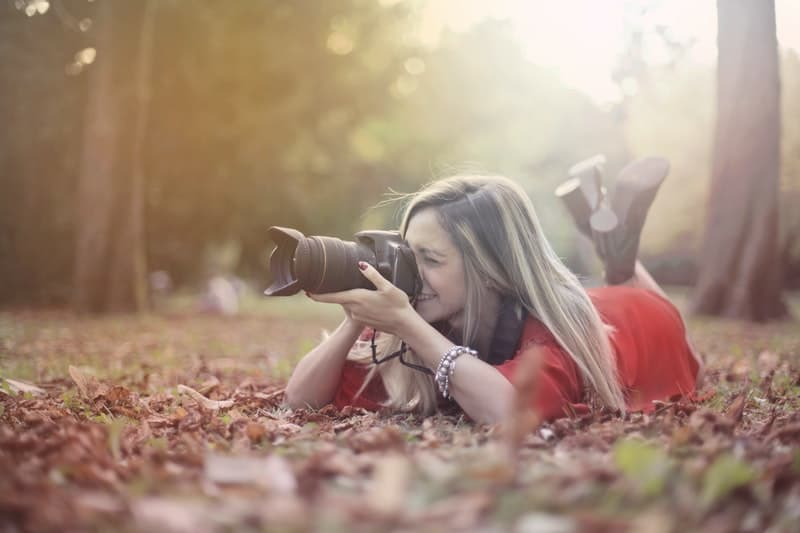 smiling woman taking photos on professional camera on dried leaves on the ground